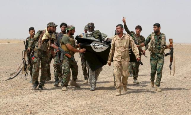 Iraq's Shi'ite paramilitaries and members of Iraqi security forces hold an Islamist State flag which they pulled down in Nibai, in Anbar province