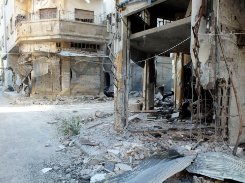 Damaged shops are pictured in Homs