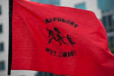 "A demonstrator holds a flag declaring ""Refugees Welcome."" A"